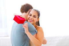 Young woman hugging her boyfriend for a gift Stock Image