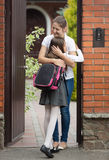 Young woman hugging her daughter in front of house after school Stock Photos
