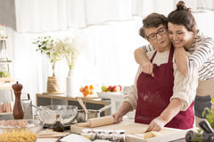 Young woman hugging her grandma. Young happy women hugging her grandma cooking in a kitchen stock images