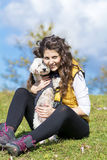 Young woman hugging her white  dog outdoor Royalty Free Stock Photo
