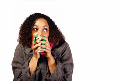 Young woman hugging a hot drink. A young mixed race woman hugs a hot drink to keep warm, whilst looking upwards to her left stock images