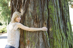 Young woman hugging large tree trunk Stock Images