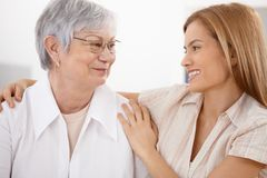 Young woman hugging mother smiling stock photography