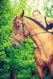 Young woman hugging and sitting on horse Royalty Free Stock Photos