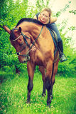 Young woman hugging and sitting on horse Stock Image