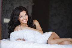 Young woman hugging a white cushion Stock Image