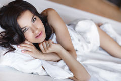 Young woman hugging a white cushion Stock Photos
