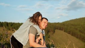 A young woman hugs her boyfriend and laughs. Happy couple in the Park. stock video footage