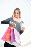 Young woman in a hurry checking time after shopping Stock Photo