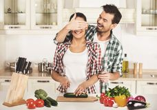 Young woman and husband are cooking with fresh vegetables. Husband shuts her eyes hand. Young women and husband are cooking with fresh vegetables. Husband shuts stock images