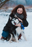 Young woman with husky dog in the winter park Royalty Free Stock Images
