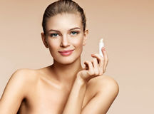 Young woman with hygienic lipstick looks at camera. Photo of attractive woman on beige background. Youth and skin care concept stock images