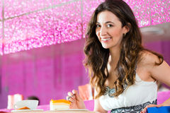 Young woman in ice cream parlor. Young woman in a cafe or ice cream parlor eating a cake, maybe she is single or waiting for someone Stock Photo