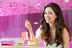 Young woman in ice cream parlor. Young woman in a cafe or ice cream parlor eating a cake, maybe she is single or waiting for someone Stock Photography