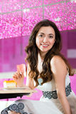 Young woman in ice cream parlor. Young woman in a cafe or ice cream parlor eating a cake, maybe she is single or waiting for someone Royalty Free Stock Photos