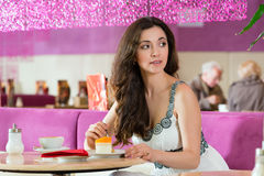 Young woman in ice cream parlor. Young woman in a cafe or ice cream parlor eating a cake, maybe she is single or waiting for someone Stock Image