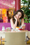 Young woman in ice cream parlor. Young woman in a cafe or ice cream parlor eating a cake and using her phone, maybe she is single or waiting for someone Royalty Free Stock Photos