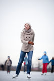 Young woman ice skating outdoors on a pond Stock Photos