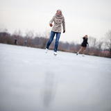 Young woman ice skating outdoors on a pond Royalty Free Stock Photo