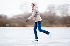Young woman ice skating outdoors on a pond Royalty Free Stock Image