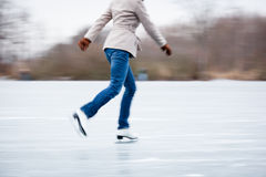Young woman ice skating outdoors on a pond Stock Images