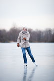 Young woman ice skating outdoors on a pond Royalty Free Stock Images