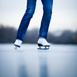Young woman ice skating outdoors on a pond Stock Photo