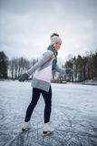 Young woman ice skating outdoors on a pond Royalty Free Stock Photos