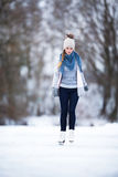 Young woman ice skating outdoors on a pond Stock Image
