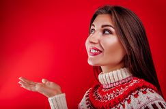 Young woman in Icelandic sweater pointing at something. Christmas or New Year celebration concept. Young woman in Icelandic sweater pointing at something on red Royalty Free Stock Photos