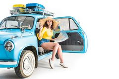 Woman sitting in car with map stock photography