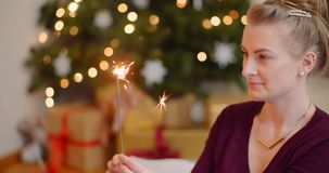 Young Woman Igniting Sparkler With Lighter At Home
