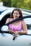 Young woman with ignition key in hand in opened door car Stock Images
