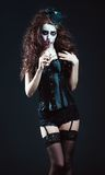 Young woman in the image of sad gothic freak clown smelling withered flower Royalty Free Stock Images