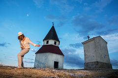 Young woman imitates guitar playing by the church on the hill. Young caucasian woman imitates guitar playing by the church on the hill Stock Images