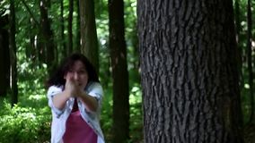 Young woman imitates shooting in the forest stock footage
