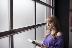 Young Woman In A Purple Shirt Reading A Book Stock Photo