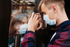 Free Young Woman In A Respiratory Mask Communicates With Her Boyfriend Through A Window. Coronavirus Covid-19 Stock Images - 183006264