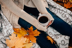 Young Woman In A Sweater And Jeans Relaxing Drink Tea On Autumn Background Stock Photography
