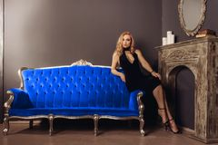 Young Woman In Black Dress Is Sitting On The Blue Couch Near The Fireplace Stock Images