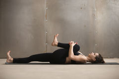 Young Woman In Knees To Chest, Apanasana Pose, Grey Studio Royalty Free Stock Images