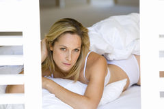 Young Woman In Underwear On Stomach On Bed By Shutters, Portrait, Close-up Royalty Free Stock Photo