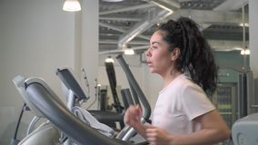 Young woman increase speed on treadmill and running. Beautiful brunette makes sport exercises in the gym. Pretty woman runs on treadmill and trains her legs and stock footage