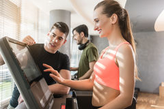 Young woman increasing the speed during a workout session superv. Motivated young women increasing the speed of the treadmill during a workout session supervised Stock Photography