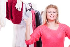 Woman in home closet choosing clothing, indecision. Young woman indecision in wardrobe home closet, teen blonde girl choosing her warm fashion outfit on clothing stock image