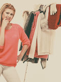 Woman in home closet choosing clothing, indecision. Young woman indecision in wardrobe, teen blonde girl choosing her warm winter fashion outfit in walk in royalty free stock images