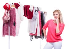Woman in home closet choosing clothing, indecision. Young woman indecision in wardrobe, teen blonde girl choosing her warm winter fashion outfit in walk in stock photos