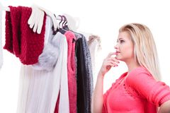 Woman in home closet choosing clothing, indecision. Young woman indecision in wardrobe, teen blonde girl choosing her warm winter fashion outfit in walk in royalty free stock image