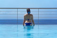 Young woman at infinity pool. Looking toward horizon over water stock images