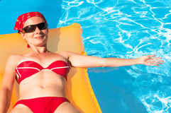 Young woman on a inflatable mattress in the pool Stock Photo